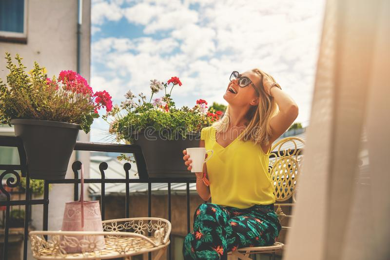 Attractive young woman enjoying vacations and drinking coffee on hotel balcony stock images