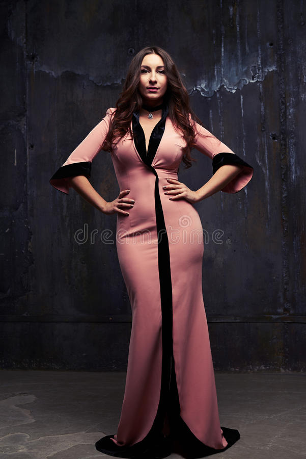 Attractive young woman in evening pink dress with hands on hips stock photo