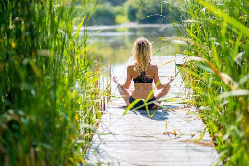 Attractive young woman exercising and sitting in yoga lotus pos stock photography