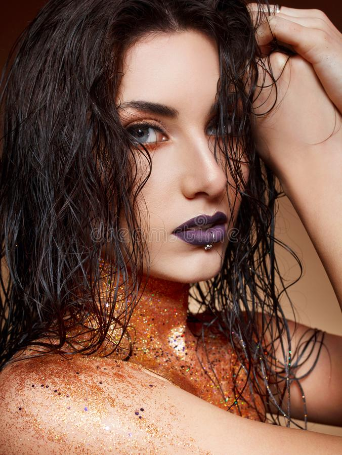 Attractive young woman with fashion make up with gold glitter on. Her neck royalty free stock photo