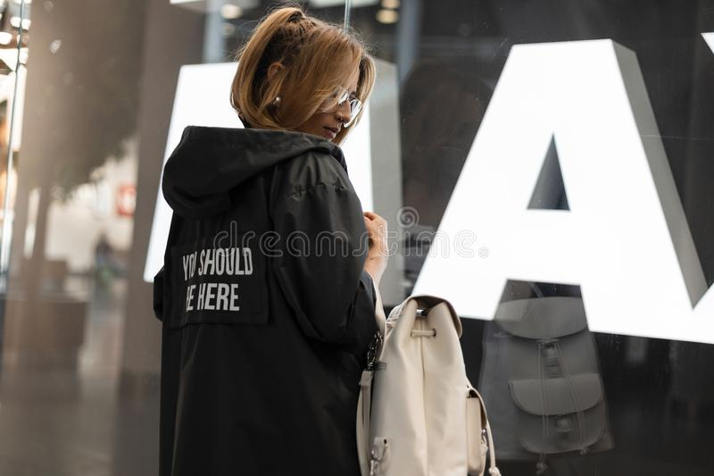 Attractive young woman in a fashionable raincoat in vintage glasses with a stylish white leather backpack is standing. Near a modern glass wall in a shopping stock image