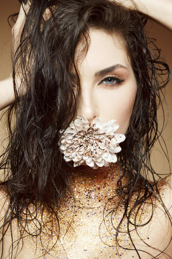 Attractive young woman with fashon make up with gold glitter on. Her neck and flower in lips stock photos