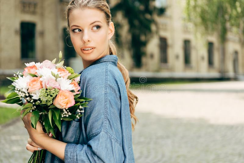Attractive young woman with flower bouquet. Looking away royalty free stock photography