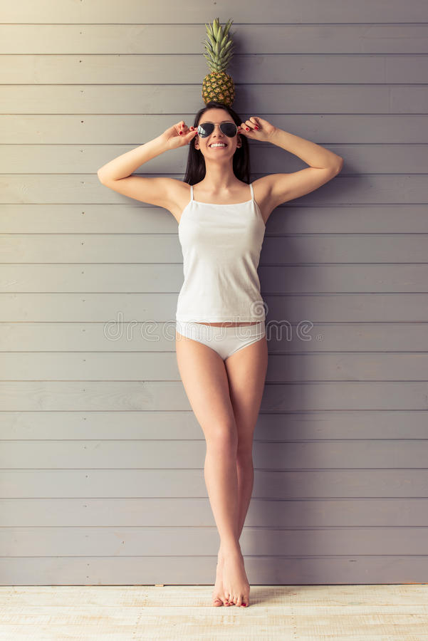 Attractive young woman. Full length portrait of attractive young woman in underwear and glasses holding a pineapple overhead and smiling, standing against grey stock photos