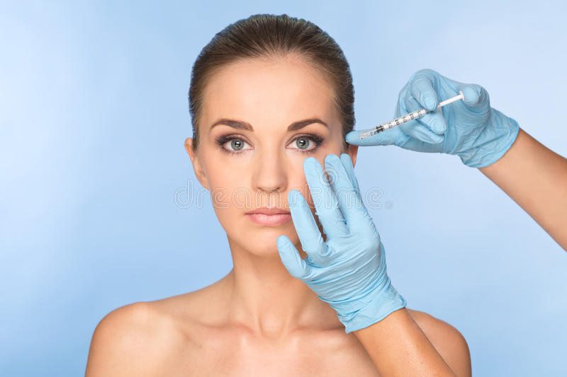Attractive young woman gets cosmetic injection of botox. royalty free stock photography