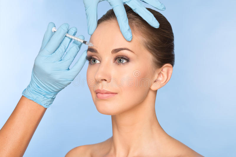 Attractive young woman gets cosmetic injection of botox. Doctors hands making an injection in face. Beauty Treatment royalty free stock photo