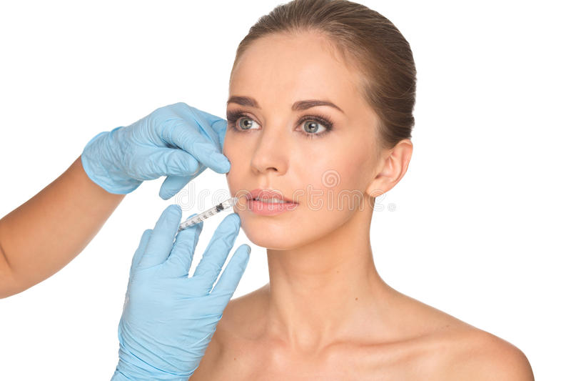 Attractive young woman gets cosmetic injection of botox. Isolated over white background. Doctors hands making an injection in face. Beauty Treatment stock photo