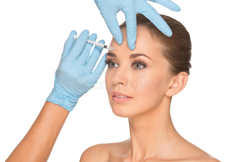 Attractive young woman gets cosmetic injection of botox. Isolated over white background. Doctors hands making an injection in face. Beauty Treatment royalty free stock photography