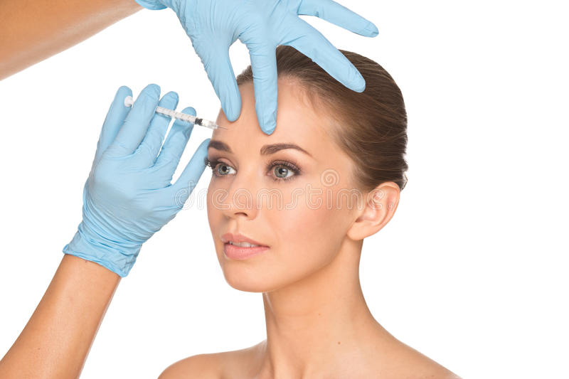 Attractive young woman gets cosmetic injection of botox. Isolated over white background. Doctors hands making an injection in face. Beauty Treatment royalty free stock images