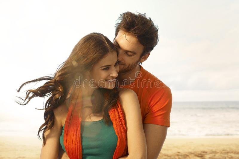Attractive young woman getting a kiss at beach royalty free stock image
