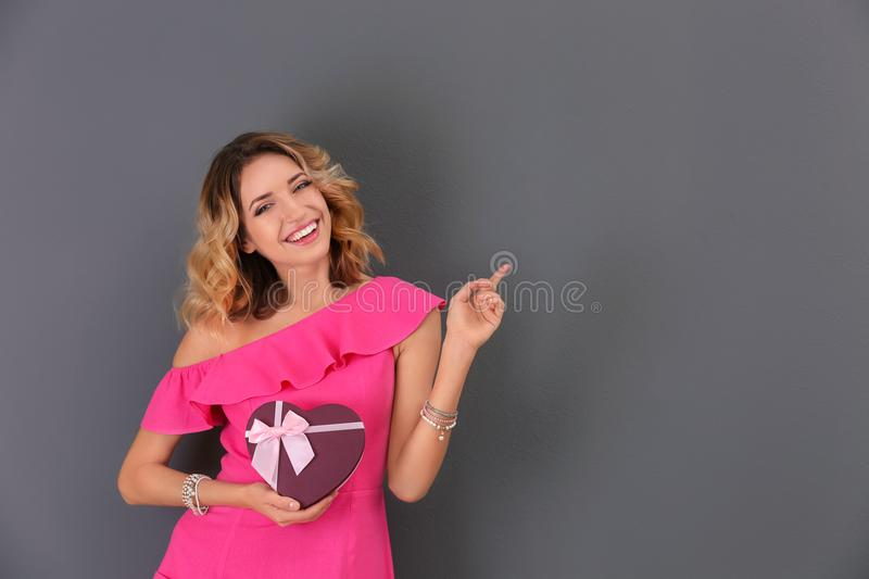 Attractive young woman with gift box. On grey background stock images