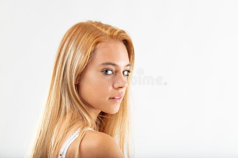 Attractive young woman glancing back. Over her shoulder, with parted lips and a thoughtful expression isolated on white with copy space royalty free stock photography