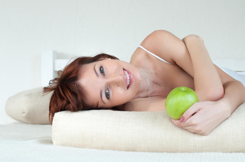 Download Attractive Young Woman With An Green Apple At Bed Stock Image - Image: 26236825