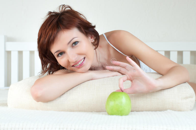 Download Attractive Young Woman With An Green Apple At Bed Stock Photo - Image: 26236852