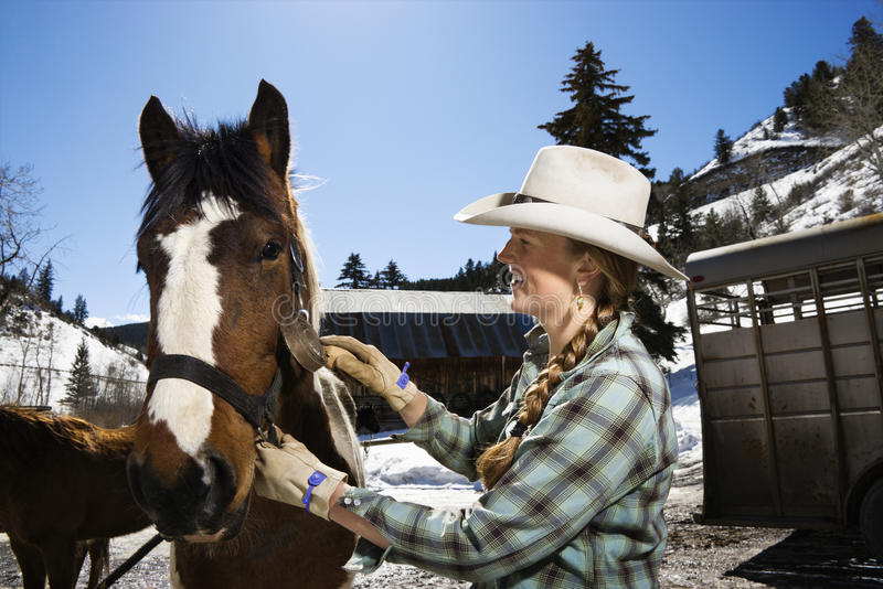 Attractive Young Woman Grooming Horse. Attractive young woman wearing a cowboy hat and grooming a horse. Horizontal shot royalty free stock photo