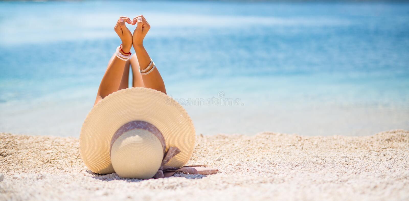 Attractive young woman with hat lies on the beach royalty free stock image