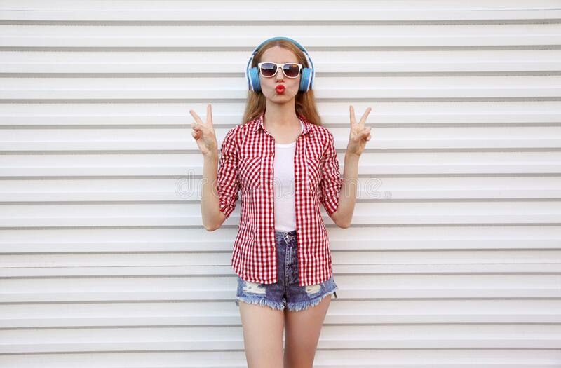 Attractive young woman in headphones listening to music blowing red lips sending sweet air kiss on white stock photography