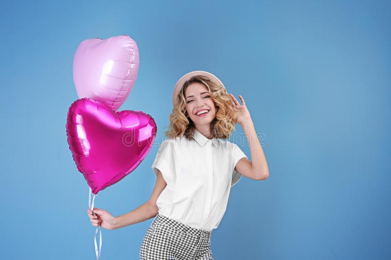 Attractive young woman with heart shaped air balloons stock photo