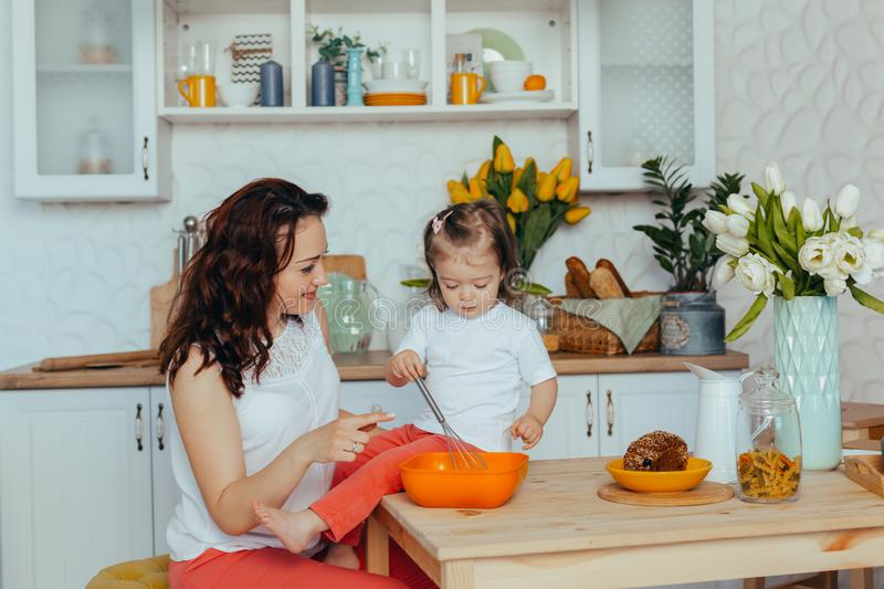 Attractive young woman and her little cute daughter are cooking on kitchen stock photo