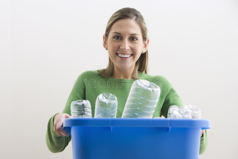 Attractive Young Woman Holding a Blue Recycle Bin royalty free stock image