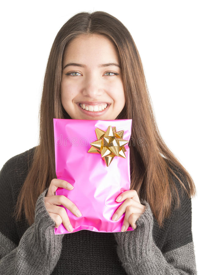 Attractive young woman holding pink present. Happy beautiful teenage girl with christmas gift in pink wrapping stock photo