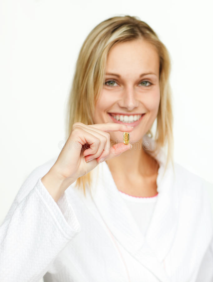 Attractive young woman holding a yellow pill royalty free stock photography