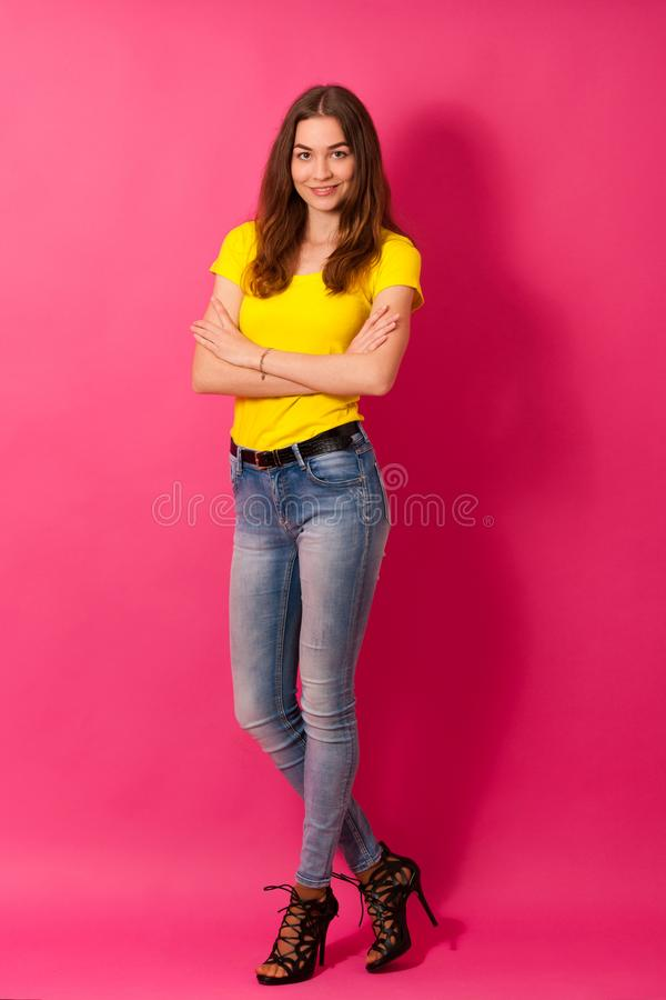 Attractive young woman in jeans and yellow t shirt over pink background - full length photo royalty free stock photos
