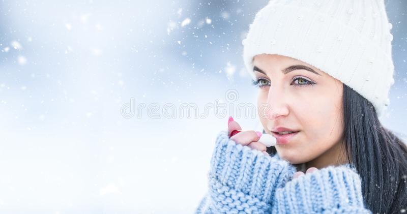 Attractive young woman l protecting lips with lip balm in snowy and frozen weather.  stock photos