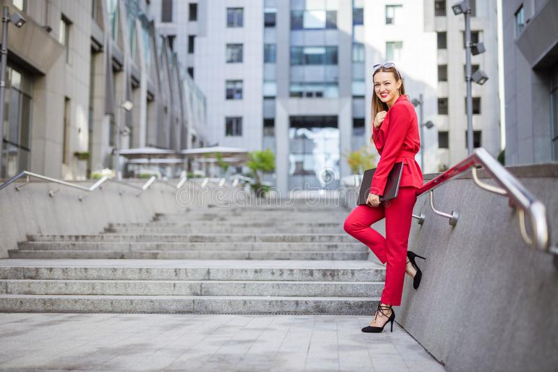 Attractive young woman with laptop outdoors in business district. Attractive young woman with laptop standing on stairs in business district stock image