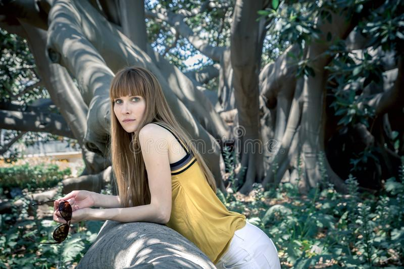Attractive young woman leaning against tree. In summer stock images