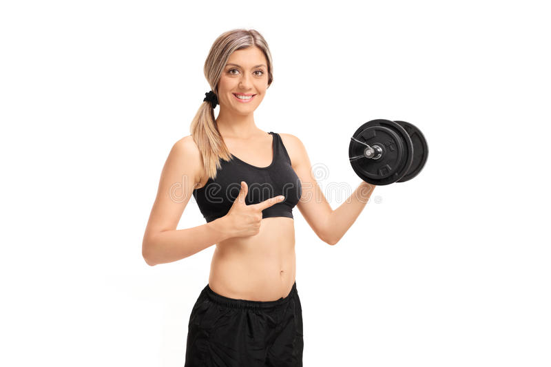 Attractive young woman lifting a dumbbell and pointing royalty free stock photos