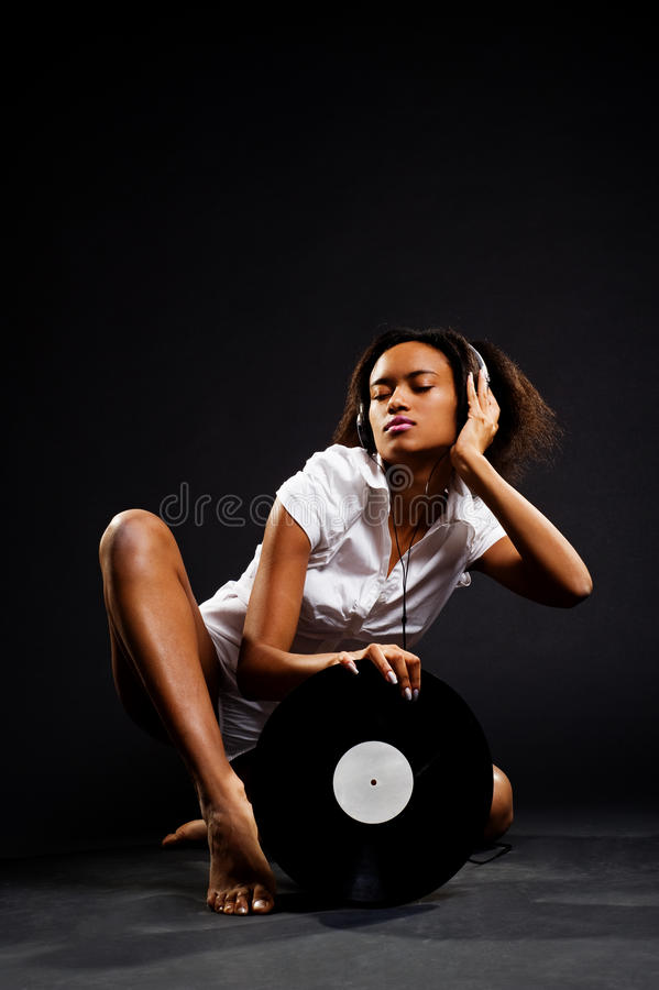 Attractive young woman listening music. And holding the vinyl stock image