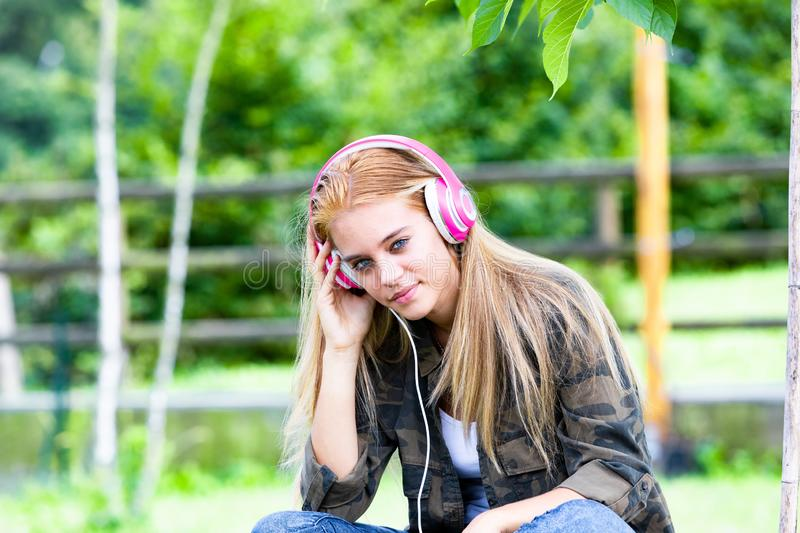 Attractive young woman listening to music. Attractive trendy young woman with long blond hair sitting outdoors in the garden listening to music on stereo royalty free stock image