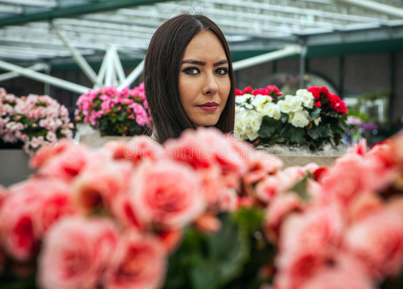 Attractive young woman with long beautiful hairs posing in flower greenhouse of Keukenhof park.  stock photo