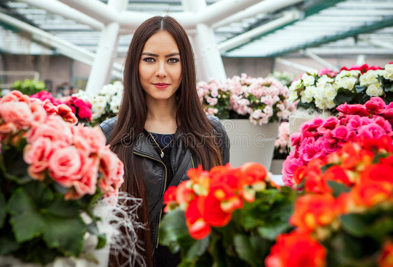 Attractive young woman with long beautiful hairs posing in flower greenhouse of Keukenhof park.  royalty free stock image