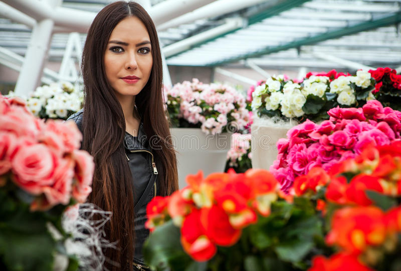 Attractive young woman with long beautiful hairs posing in flower greenhouse of Keukenhof park.  stock photography