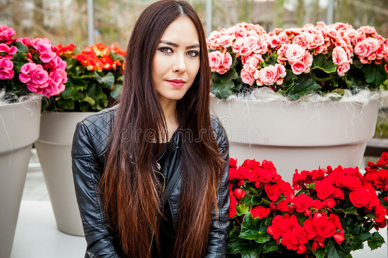 Attractive young woman with long beautiful hairs posing in flower greenhouse of Keukenhof park.  stock image