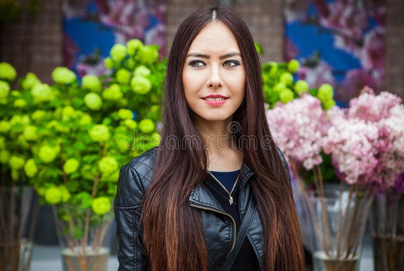 Attractive young woman with long beautiful hairs posing in flower greenhouse of Keukenhof park.  royalty free stock images