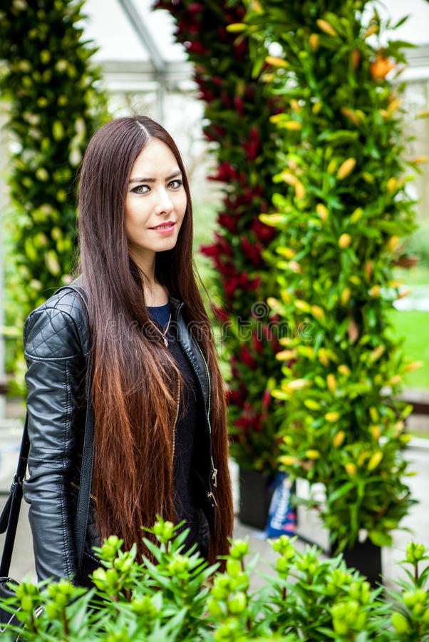 Attractive young woman with long beautiful hairs posing in flower greenhouse of Keukenhof park.  royalty free stock photos