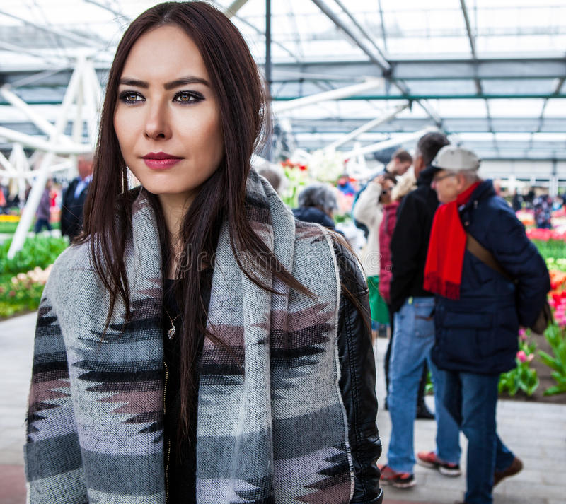 Attractive young woman with long beautiful hairs posing in flower greenhouse of Keukenhof park.  royalty free stock photography