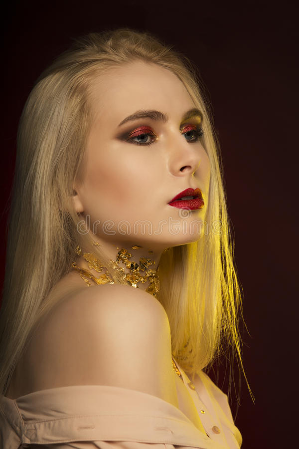 Attractive young woman with long blonde hair and patterns of golden foil on her skin, posing on the black background stock images