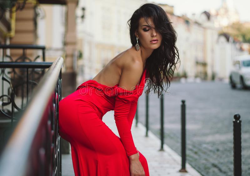 An attractive young woman in a long red evening dress is walking around the city.Fashion photo royalty free stock photo
