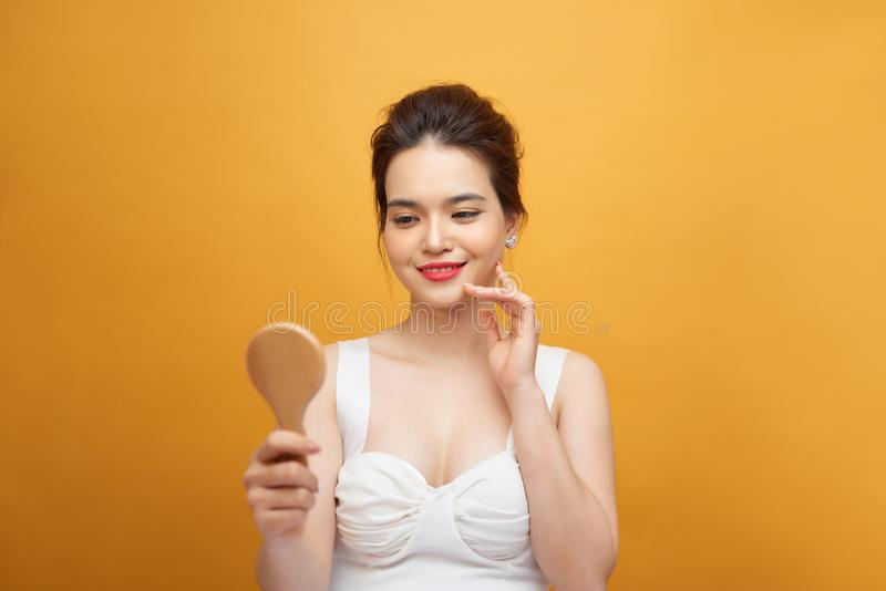 Attractive young woman looking into hand mirror on yellow background royalty free stock image