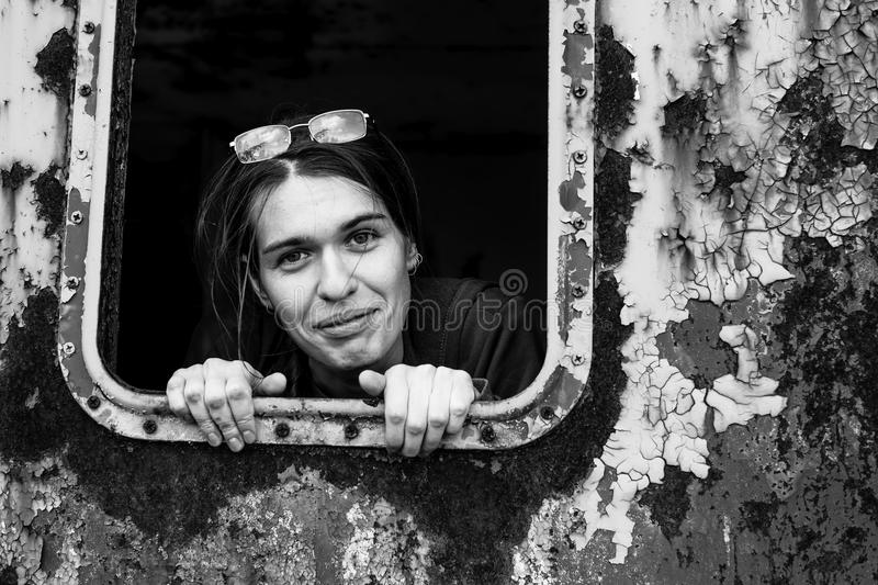 Attractive young woman looking out of the window metal caboose. royalty free stock images