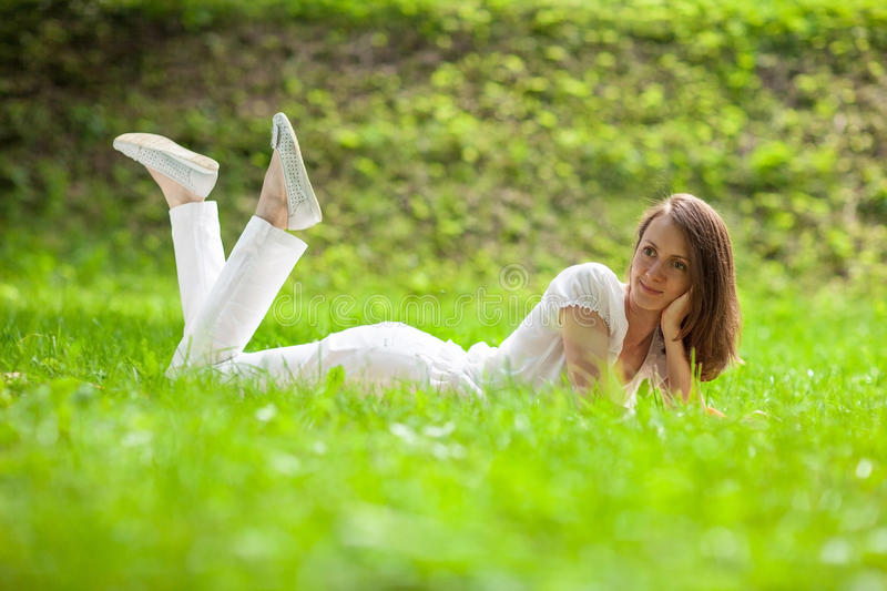 Attractive young woman lying on green grass royalty free stock images