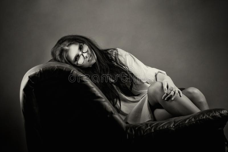 An attractive young woman is lying on a leather sofa. royalty free stock image