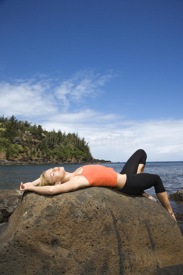 Attractive Young Woman Lying on Rock at Beach stock photos