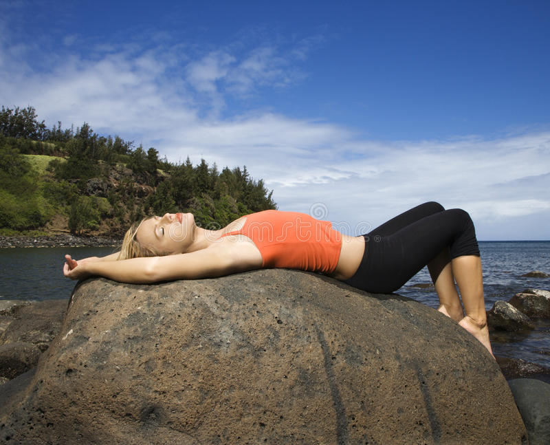 Attractive Young Woman Lying on Rock at Beach royalty free stock images