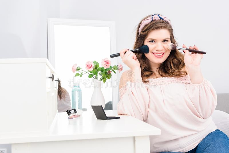 attractive young woman with makeup brushes in hands looking at camera stock image