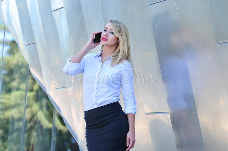 Attractive young woman making business call on her smart phone royalty free stock photography